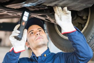 Mechaniker beleuchtet Auto
